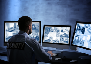 Security guard watching video surveillance on three monitors