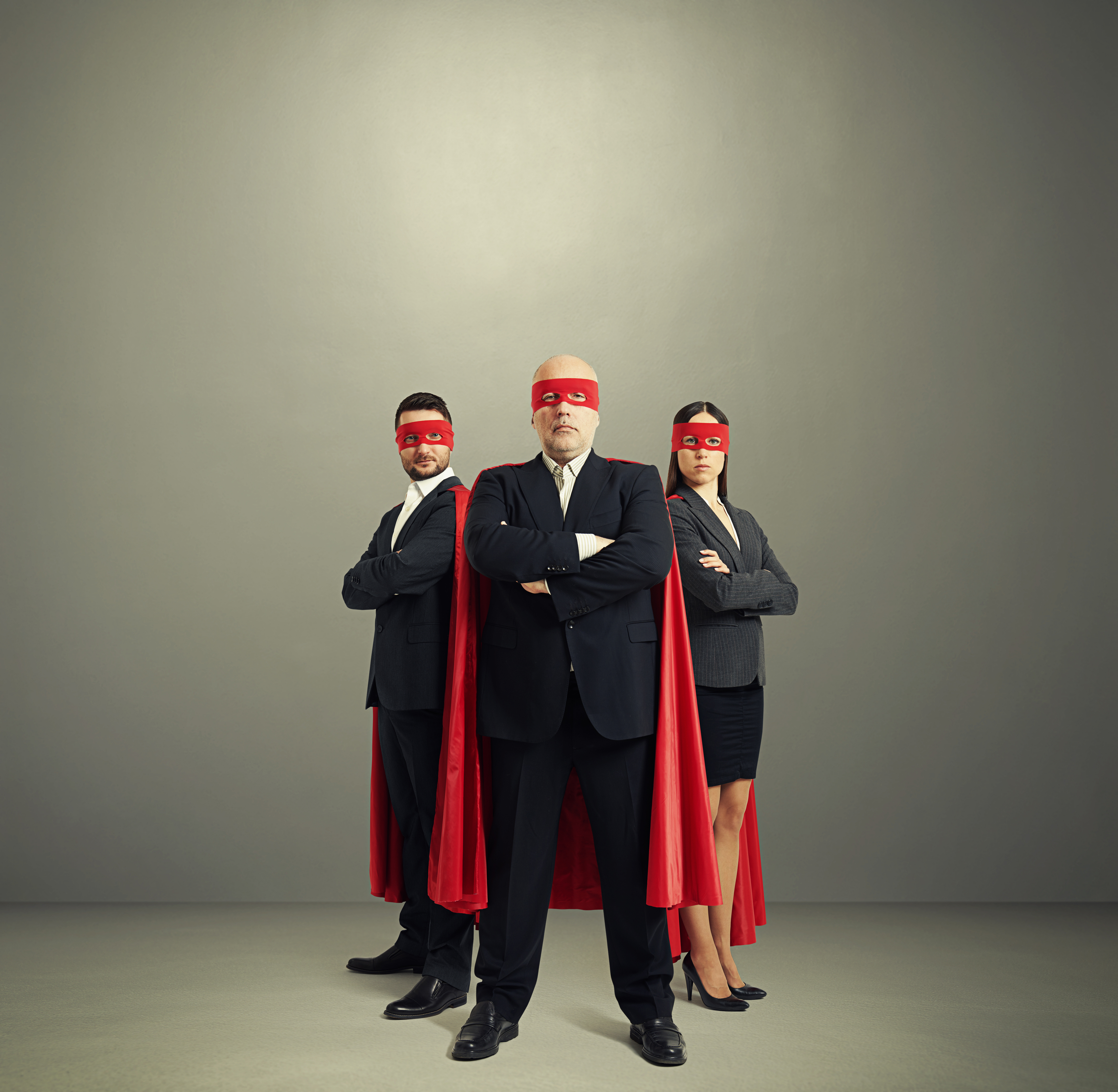Three business people penetration testing super heros with red capes and eye masks